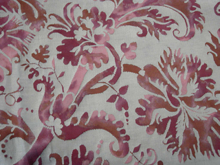 The ground fabric has a marbled effect in shades of pink and red, possibly achieved with a partial discharge technique, then overprinted with silver metallic ink in an arabesque pattern.