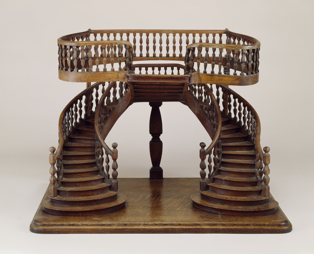 """Double-revolution staircase model with curved double staircase with baluster railings, joining on a central landing from which a reverse single staircase rises at right angles, leading to a balcony; this staircase model is similar to one described as being """"in Renaissance style for a store"""", in plate 17 of a folio by E. Delbrel, published in Paris in the 1880's."""