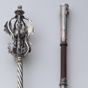 Thin cylindrical shaft with upper half spirally turned, lower half plain.  Finial of four curved wires, each with two applied oak leaves, encircling sphere on shaft and capped by small scallop-edged finial with tiny knob on top.  Pointer is right hand with middle finger extended and banding above wrist.