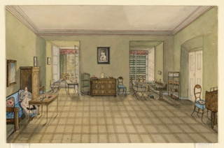 Interior view of a room with windows, furnished with wooden chest, tables, chairs, and shelving. A woman sit, crocheting, on a couch on the left.