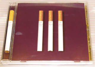 """CD cover design for Jamie Block's """"Timing is Everthing"""".  CD case is clear plastic. CD insert folds into four sections. Cover: Color photographic reproduction of three cigarettes with brown filters on marron background.  On each cigarette, imprinted """"Block"""" (in red) and each word of the title: """"TIMINIG IS EVERYTING"""" (in black). There is one acutal """"Rothman Special"""" cigarette in the spine of case.  Opening insert: letter forms spelling the name """"Block"""" are depicted as taped together boxes forming block-shaped letters. Inside four pages contain credits, song list, and black and white photographic reproductions of artist at top center, three photographs of smoked cigarettes at lower left, scotch on the rocks at lower right, and city view (roof tops of apartments) at far right.  On yellow background, on one of exterior pages, color photographic reproduction of artist in hot tub and ciagarette.  Back of CD insert: black and white photographic reproductions of ashtray (in aerial perspective), of rhinoceros and of two smoked cigarettes at upper right.  Imprinted at right center: """"PRODUCED BY/ MARK HUTCHINS www.blocknyc.com & JAMIE BLOCK...""""(in black handwriting font).   CD: black and white photographic reproduction of ashtray (same one on back of CD insert).   Back of case: divided into 2 by 7 grid on marron background.  Each cell labelled 1through 13 according to track number of CD.  Each cell contains color photographic reproduction of smoked cigarette, elapse time of song, and title. In last cell, imprinted: """"Promotional Use Only/ Not for Sale/ PRODUCED BY/ Mark Hutchins/ & Jamie Block..."""" (in white)."""