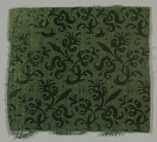 Fragment of dark green velvet with a design in cut pile of small flowering branches in horizontal rows turning alternately right and left. Ground in uncut pile.