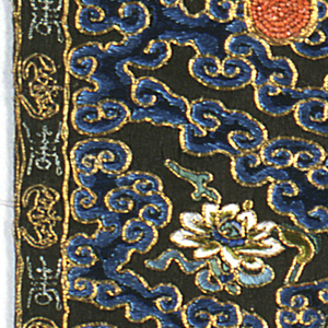 Mandarin square for civil official of the second rank. A golden pheasant, embroidered on black, in flight and surrounded by cloud forms and symbols.  The two pieces, meant for the front of a coat, have been sewn together.