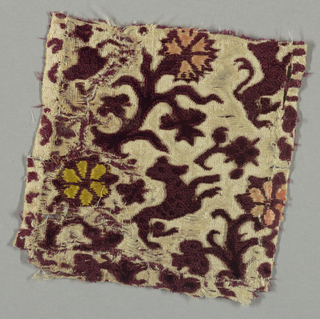 Small fragment of red cut and uncut velvet on a white satin ground in a pattern of flowers, rosettes, leafy sprigs and rampant animals.