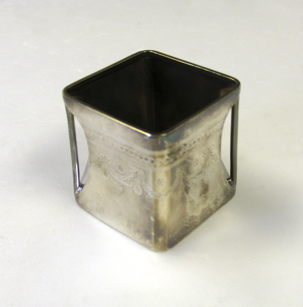 "Square ""cube"" body, flat base, open top.Gilded interior.At opposing cornersconcave indentations with vertical strut handles. Bright-cut engraved in swags around upper body. Square cube body. Open top, gilded interior. Two opposed corners with in- set vertical handles. Bright-cut engraving of garlands encircle all sides."
