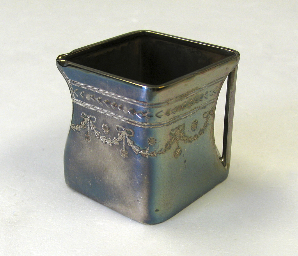 """Square """"cube"""" body, flat base, open top.Gilded interior. Corner concave to form pouring lip; opposite corner concave with verticle strut handle. Engr-aved with bright-cut swags around upper body."""
