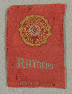 "Red tobacco silk from Egyptienne Luxury cigarettes with seal of Rutgers University in yellow and white. Just below is ""Rutgers"" in white sloping capital letters."