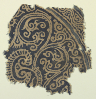 "Unbleached cotton cloth resist-printed in two shades of blue.  Fragment of a motif, more or less circular, reserved in ground color.  Center: vine pattern curving inward to frame actively curved foliage (""raisins a appendice"") and part of a palm leaf on fan-shaped leaf in profile.  Small segment of a curved border shows remains of bands in lighter blue."