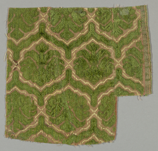 Fragment of cut and uncut green velvet in a pattern of palmettes enframed in a hexagonal lattice. Palmettes alternately face up and down.