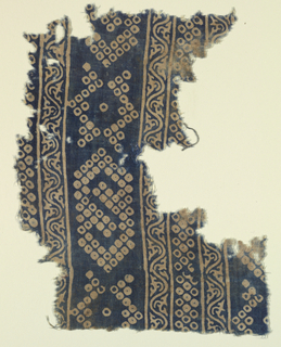 Fragment of border in fine cotton plain cloth.  Design in white on dark blue ground, arranged in horizontal bands.  Vine motif, and geometric ornament formed by blocks of small white squares with blue centers.