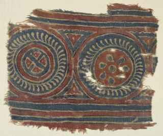 Unbleached plain weave cloth.  Design in blue and red.  Two circles, approximately 21 cm in diameter: one in blue with white detail, red center with blue heart-shaped detail; the other, similar framing smaller circle with crossed bars in center.  Above and below, borders of blue stripes.  Printing crude.