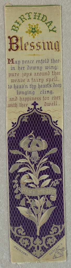 "White ribbon with a purple medallion showing white lilies and the words ""Best Wishes"" on a curving white banner. Above this is a woven inscription that reads ""Birthday Blessing"" at the top. Just below a passage reads ""May peace enfold thee in her downy wing; pure joys around thee weave a faire spell, to heav'n thy hearts deep longing cling, and happiness forever with thee dwell."""