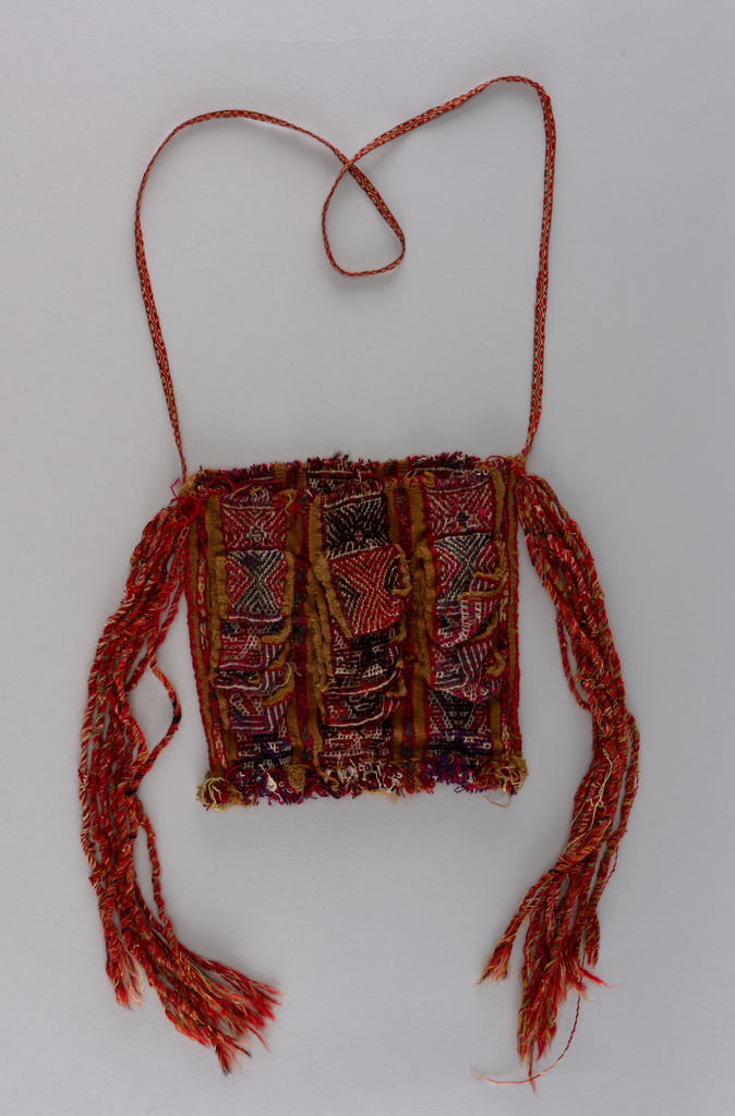 Bag with warp patterned design. Four pockets of each of the three major stripes on the front of the bag. Tassels at each side of nine narrow woven bands with long twisted warp ends. Narrow woven strap as handle.