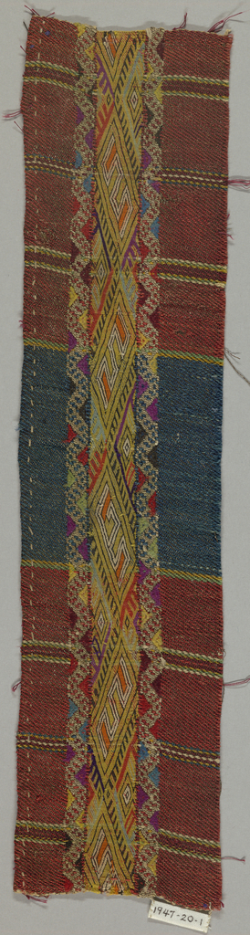 Band of embroidery in geometrical design work in yellow, orange, blue, purple, black and white silks in stem stitch; ornamental woven border in twill-weave cloth of broad stripes of reddish-brown and blue with narrow stripes of green, blue, yellow and white silk and silver metallic thread