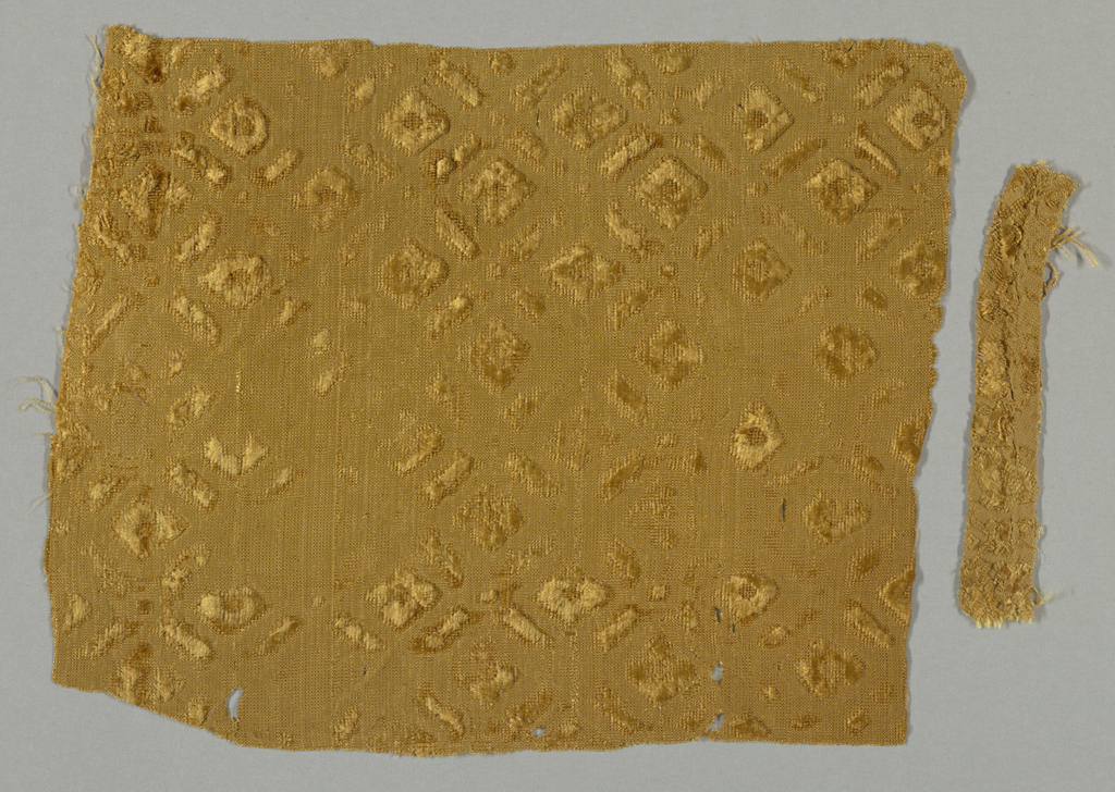 Fragment of golden tan cut and uncut velvet on self-colored ground. Geometric design of diamond-shaped motifs within larger lozenges.