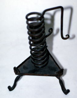 A tripod base twisted feet and a triangular platform with scrolling corners. The stem is a wire spiral that extends to form a handle with scroll finial.