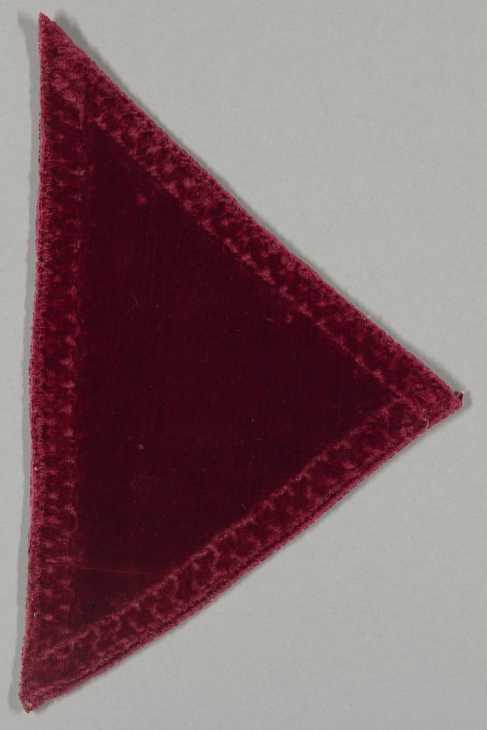Triangular fragment of red velvet.