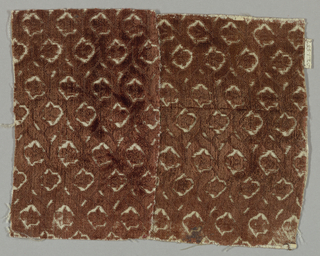 Leaves in interlaced strapwork in brown on white.