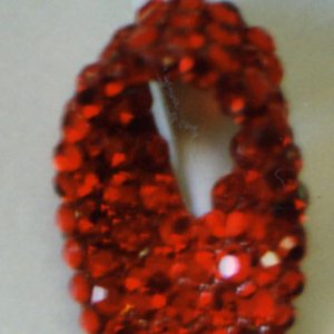 In the form of a red gem-studded looped red ribbon.
