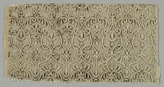 Delicate white velvet interlacing scrolls which were originally outlined with black velvet (now almost all worn away) on a metallic silver ground. Selvage at one side.