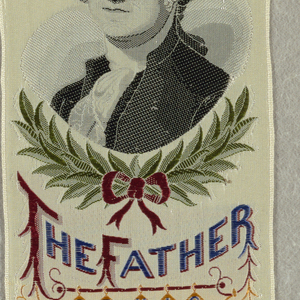 """White ribbon, brocaded in blue, green, yellow, and black. Portrait of Gorge Washington with inscription """"The Father of his Country"""" and shield."""