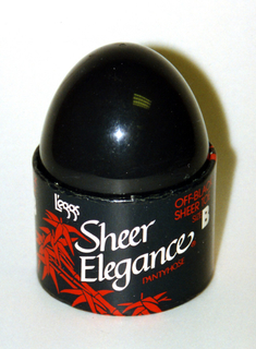 """Oviod black plastic dome in cylindrical cardboard collar decorated with bamboo shoots printed in red, the words """"L'eggs"""", """"Sheer Elegance"""" in white, and additional product information in red."""