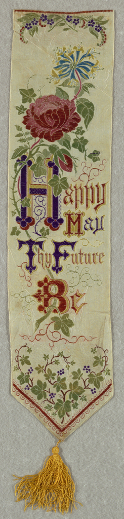 "White ribbon with a spray of roses, lilies and curling vines of ivy entwined within the words ""Happy May Thy Future Be."" Finished at the bottom with yellow tassel."