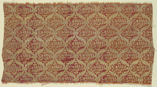 """Red-orange ground with small lattice pattern in gold, enclosing Kufic inscription: """"garment of health."""" Warps of red-orange silk covering surface except where red weft, of cotton, shows through worn parts. Extra weft of gold, wound on a silk core, forms pattern and floats on back as in brocading."""