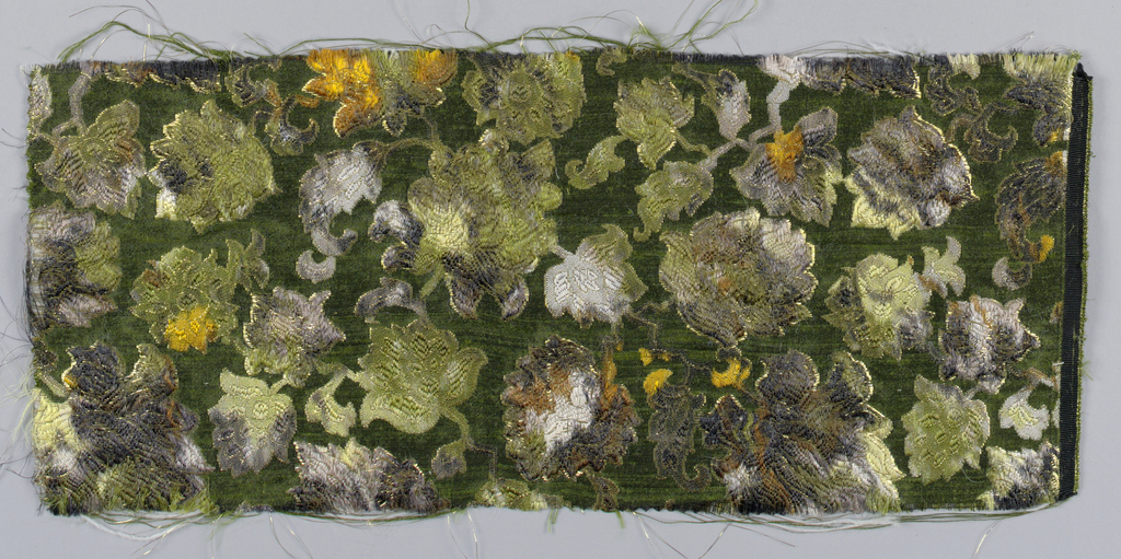Fragment of Matelasse, warp-printed and hand-cut of wool, metal and rayon showing a floral all-over pattern with quilted effect.