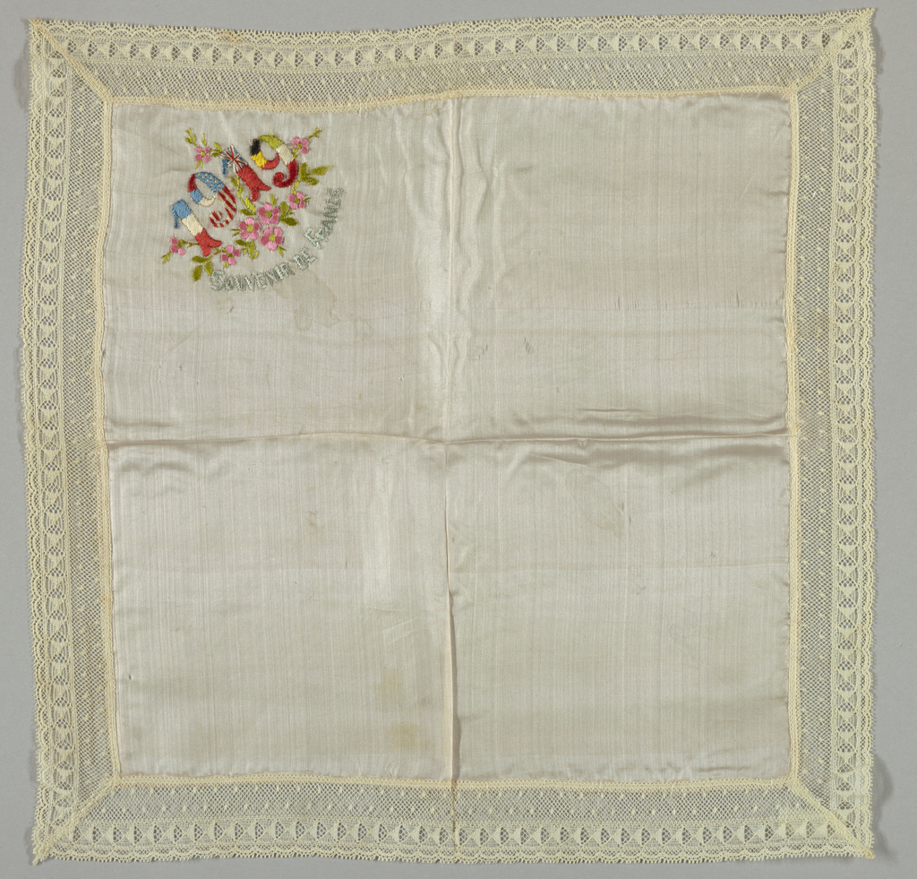 """Offwhite square of fabric with one corner embroidered with flowers, """"1919"""", and """"Souvenir de france"""" in bright colors. Each number of the date colored to represent France, the united States, England and Russia. Trimmed with 3.5cm (1 1/2in. wide machine-made lace, mitered in each corner."""