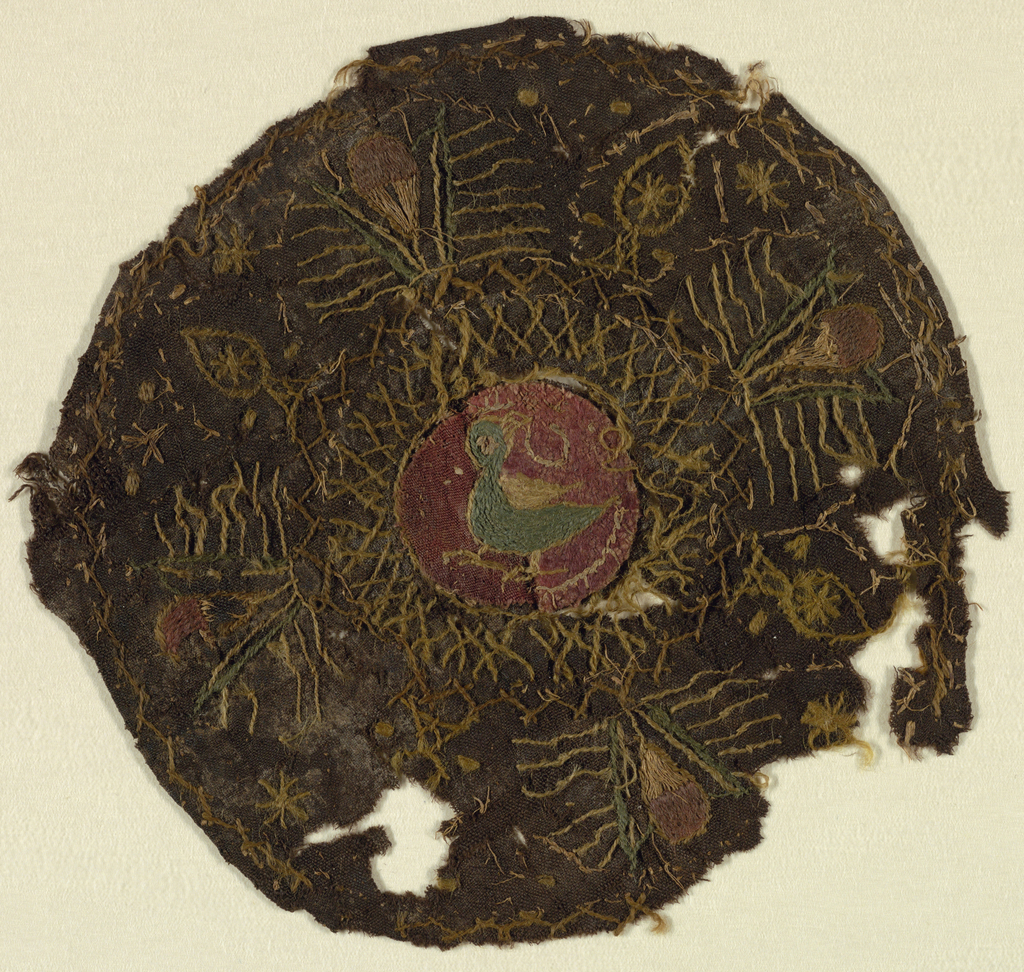 Embroidered medallion with an appliquéd bird in the center.