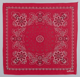 Square bandannas: -a has red ground with design in black and white; -b has deep blue ground with design in white. Deeply scrolled floral border enclosing a field of small diamonds surrounding a center floral medallion. Narrow outer border of small tangent circles with flowers in the center.