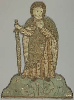 Embroidered figure of saint wearing robe and holding a staff and a book; placed on green satin ground, with embroidered flowers.
