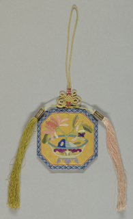 Case of yellow satin, appliquéd and embroidered with a vase and plant in colored silks. Bound in braid and fitted with yellow cord, knots, and tassels.