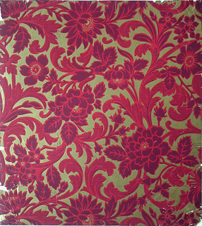 Large-scale pattern of foliate scrolls set with roses. Printed in reds and golds on gold field.