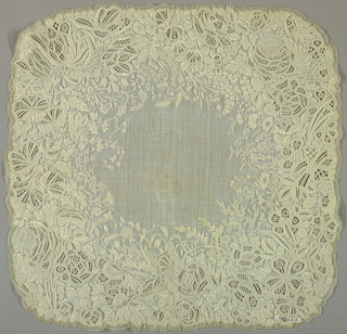 Handkerchief of fine sheer linen with deep border solidly embroidered in ornamental floral motifs. Lace trimmed.
