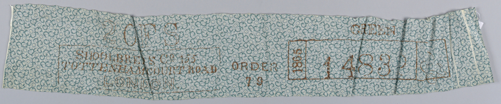 Small, tight design of 'C' scrolls turned in various directions, dots and circles in green on white.