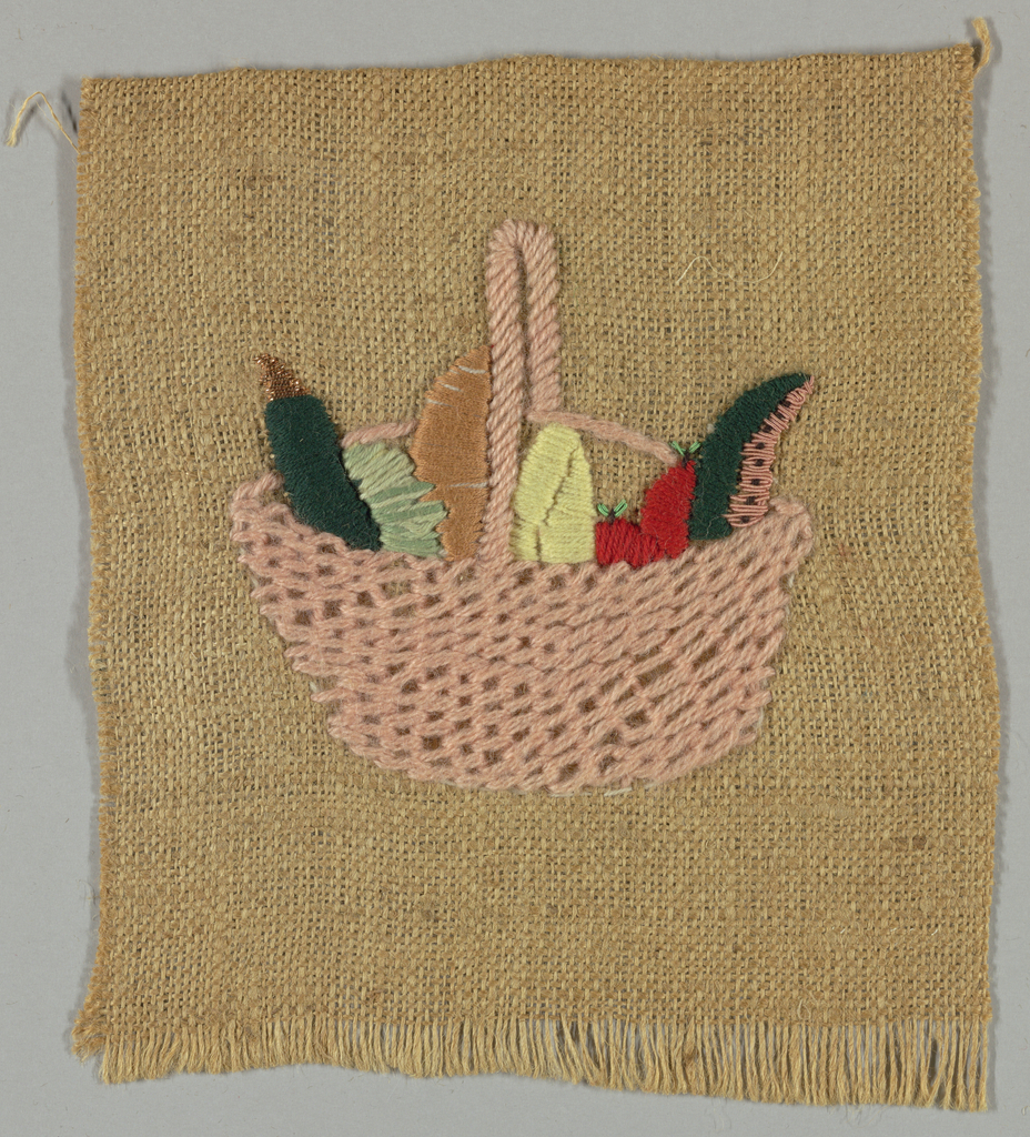Square of light brown burlap emboridered in pink, red, green, dark green, gold, and yellow in design of a basket filled with vegetables.