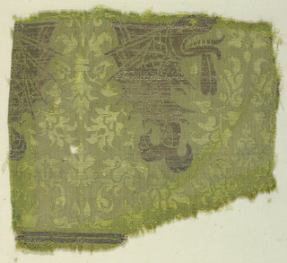 Addorsed dolphins in metal threads on a green ground with small scale floral and palmette forms. Horizontals bands of metal threads at the bottom indicate that this fragment came from the bottom of the fabric.