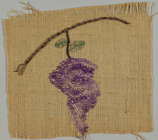 Square of light brown burlap embroidered in purple, green and brown thread showing a design of grape clusters.