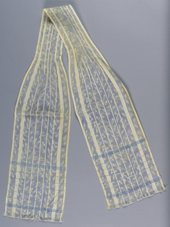 Long tie with pleats at the center and fringe at ends. The fabric is striped, white alternating with chiné print in blue, black and white. Blue stripes at end.