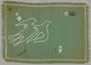Table mat of green burlap embroidered in white and metallic thread. Pattern, in the form of birds, achieved by using tape and applique.