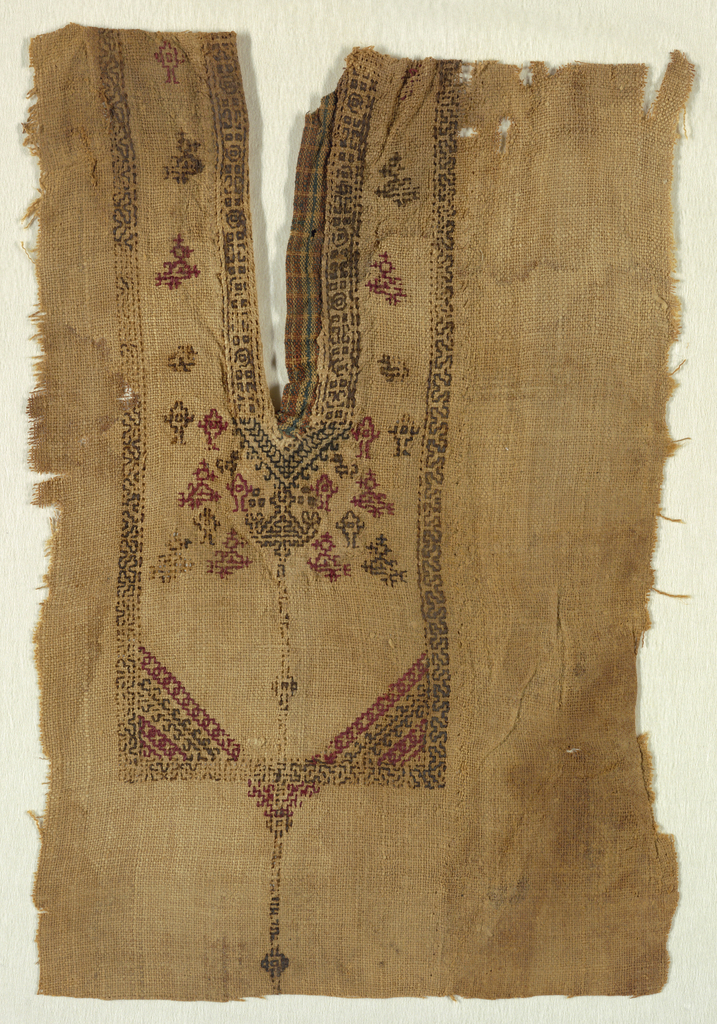 Fragment of a shirt front with an embroidered yoke of small, multicolored geometric patterning.