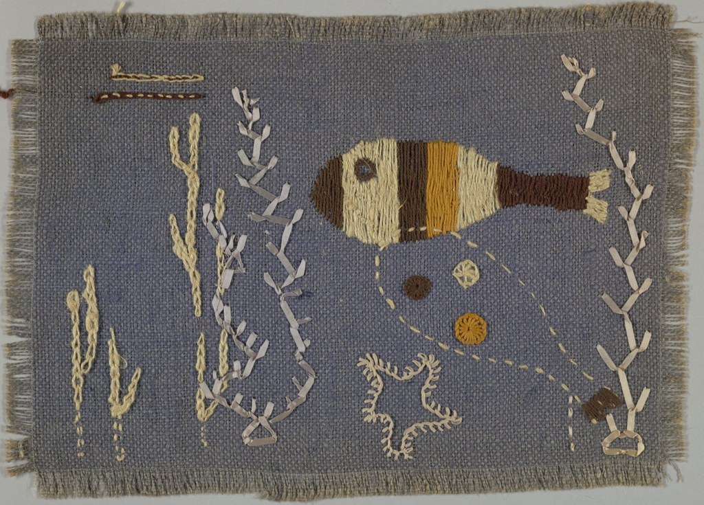 Place mat of  purple burlap embroidered in brown, gold and yellow in a stylized fish pattern and seaweed.