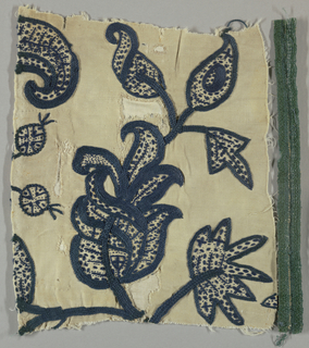 Twill weave cotton embroidered in dark blue crewel. Stylized floral forms and leaves. Left edge shows green wool braid.