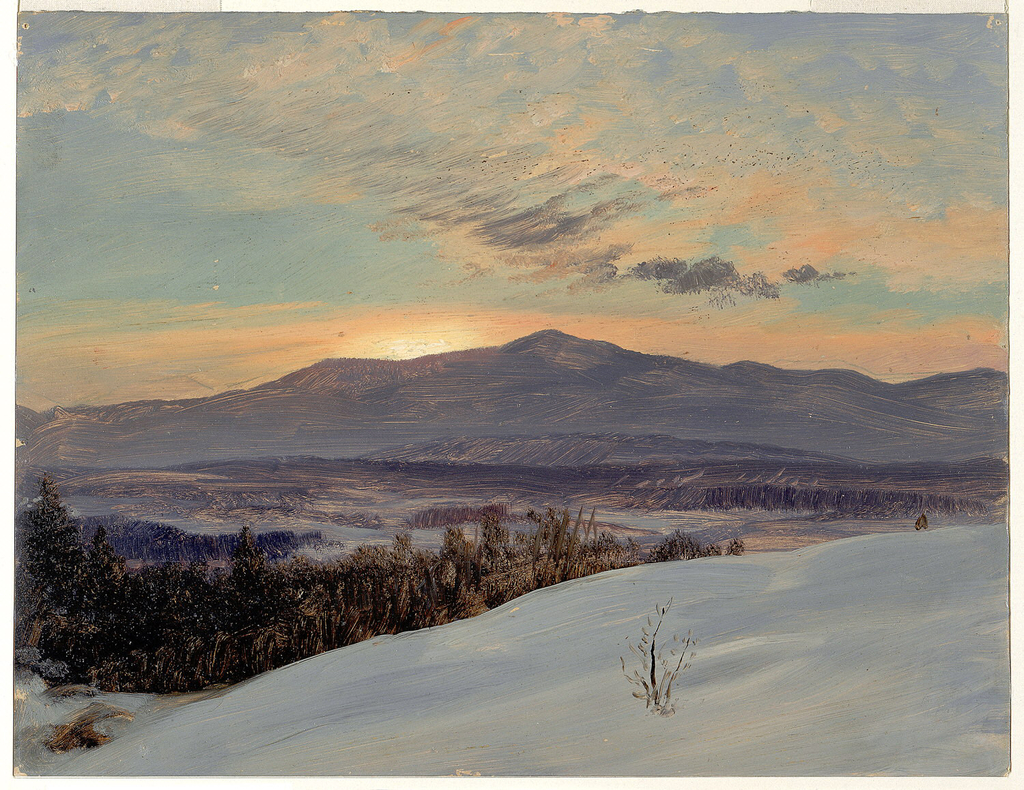 A snow covered slope in the right forground frames a sunset view across a valley in the Catskills.