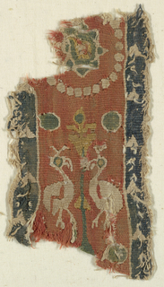 Tapestry band in Sassanian style shows two pelicans on either side of a conventionalized tree of life. Pearl roundel above encloses an eight-pointed star.