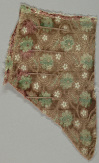"""Small-patterned or """"miniature"""" velvet with a white satin foundation. Velvet ground originally rose colored, but now faded to an allover tan color. Slender serpentines with serrated leaves and rosette-like flowers largely in uncut pile with some details in cut pile or voided. Design in green pile and white ground. Part of a man's coat; three false buttonholes."""