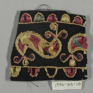 Black fragment embroidered with scrolling forms and guard borders.