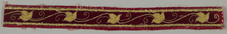 Narrow band with an appliqué of leaves in yellow on red.